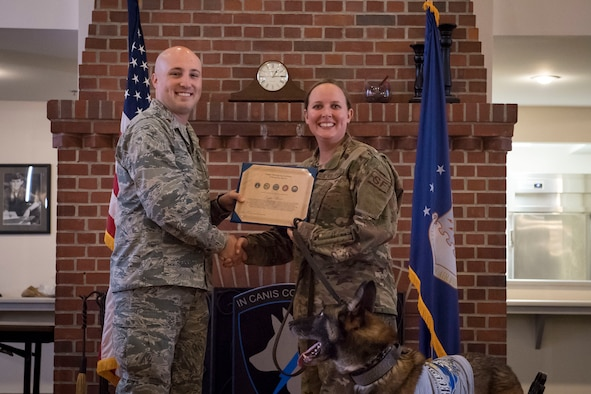 Maj. Daniel Land, 23d Security Forces Squadron (SFS) commander, poses for a photo with Staff Sgt. Lyndsay Gebhart, 23d SFS military working dog handler, after presenting military working dog ZIPPO with a Meritorious Service Award during a retirement ceremony, Feb. 21, 2019, at Moody Air Force Base, Ga. ZIPPO was assigned to the 325th Security Forces Squadron at Tyndall Air Force Base, Fl. in Nov. 2011, as a patrol/explosive dog. During his eight years on active duty, he's deployed to Saudi Arabia twice and supported four United States Secret Service missions where he provided security for the President and Vice President of the United States. (U.S. Air Force photo by Senior Airman Janiqua P. Robinson)