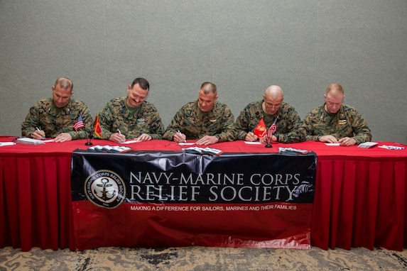 U.S. Marines with the 2nd Marine Aircraft Wing (MAW) command deck, including Brig. Gen. Karsten S. Heckl, center, the commanding general of 2nd MAW, sign donation forms during the Navy-Marine Corps Relief Society (NMCRS) Fund Drive Kick Off at Marine Corps Air Station Cherry Point, North Carolina, Feb. 20, 2019.