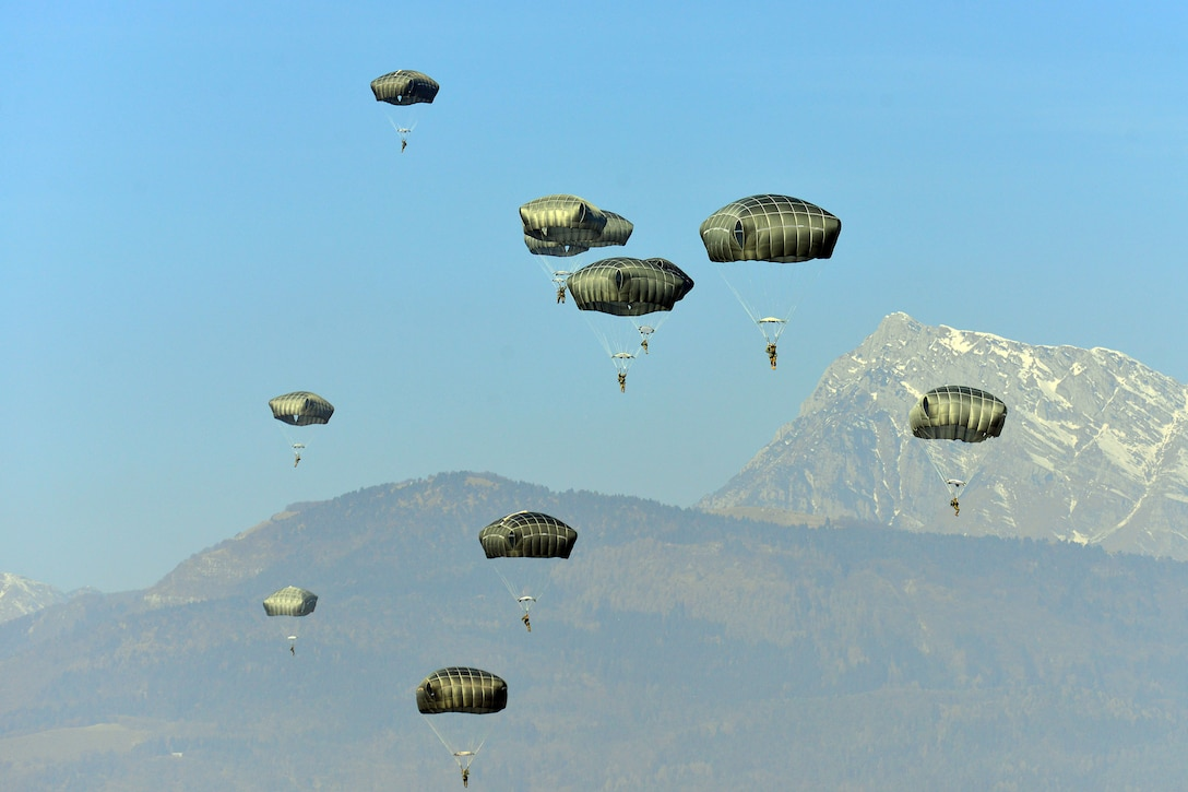 Paratroopers land on a drop zone.