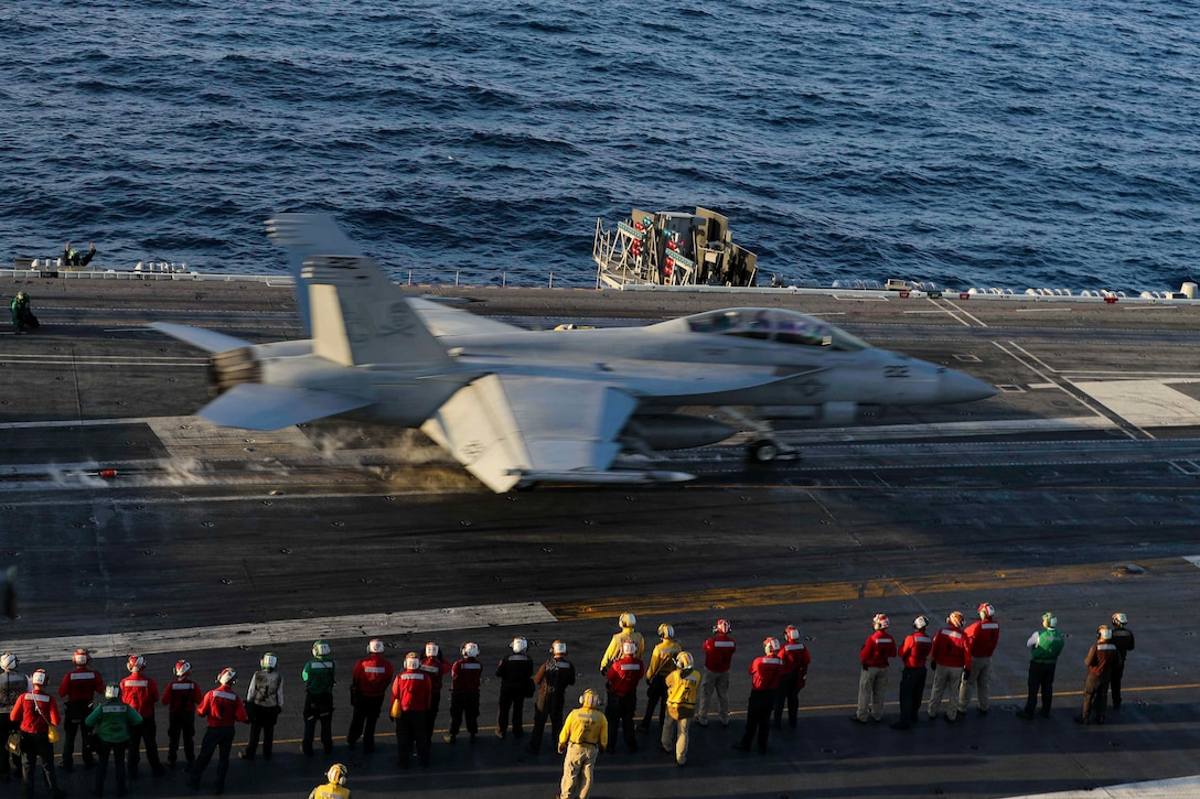 A jet takes off the flight deck of a ship.