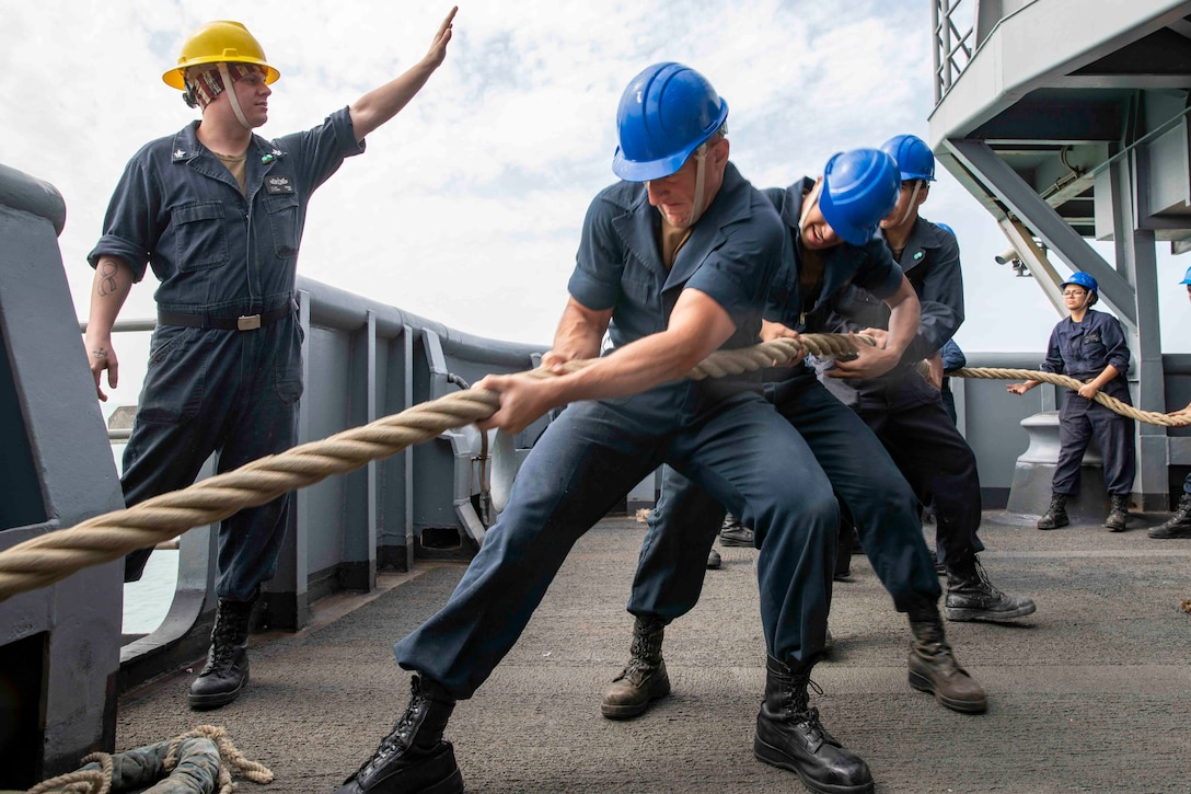 Sailors pull a line as a ship arrives at a port.