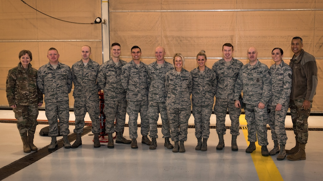 General posing with Airmen for group photo.