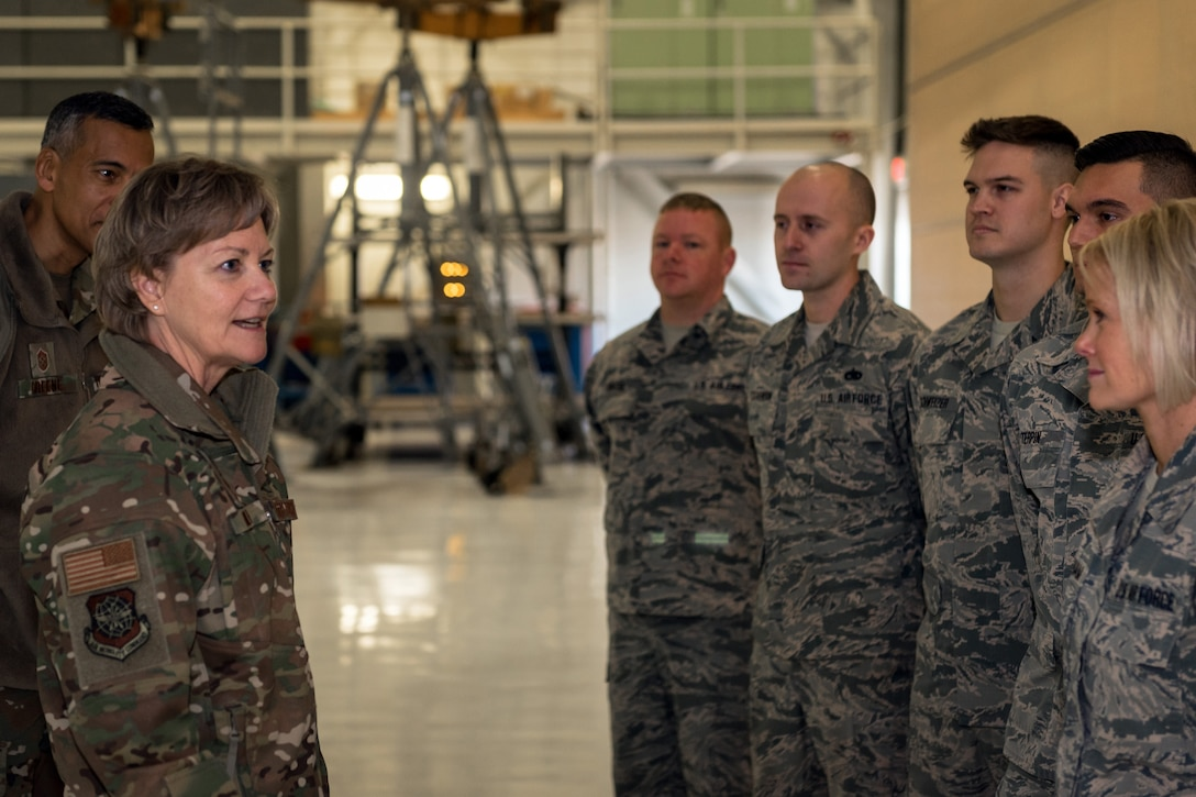 General talking with Airmen in aircraft hangar.