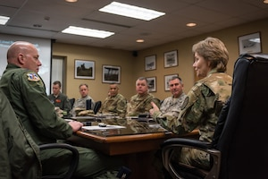 General talking with military members at table.