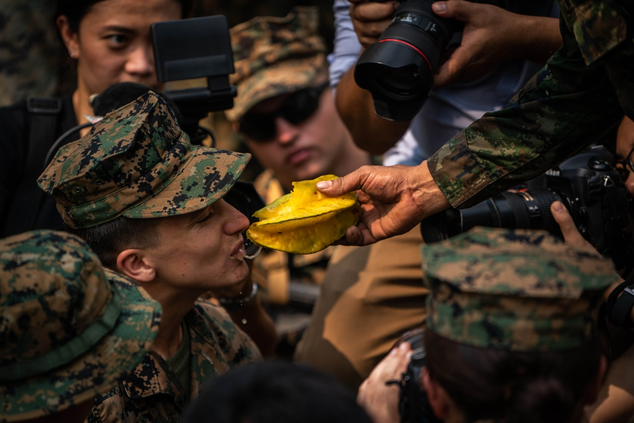 A Marine takes a bit of  star fruit during jungle training.