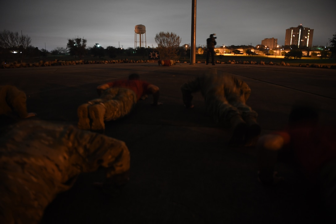 Hundreds of Special Tactics Airmen, trainees, and supporters perform memorial pushups to kick off the Special Tactics Memorial March Feb. 22, 2019, at Lackland Air Force Base, Texas.