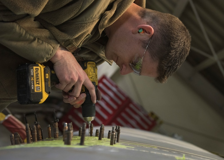 Master Sgt. Andrew Liederbach, 386th Expeditionary Maintenance Squadron combat metals flight chief, inserts temporary placeholders where the rivits will be placed after the permanent patch is complete at an undisclosed location in Southwest Asia, Feb. 6, 2019. When the damage first occurred, Liederbach and his team got their tools and materials together to fly to the aircraft to place a temorary patch on the wing to get it back to base for a permanent repair.