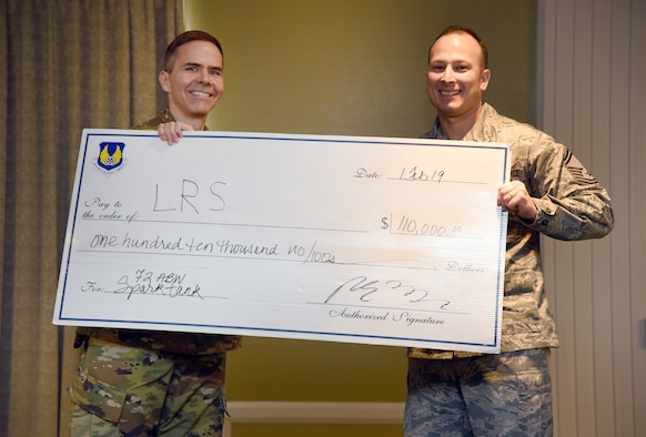 Col. Ralph Taylor, 72nd Air Base Wing vice commander, left, presented Senior Master Sgt. Francisco Zamorano with the top prize in the Spark Tank competition Feb. 1.