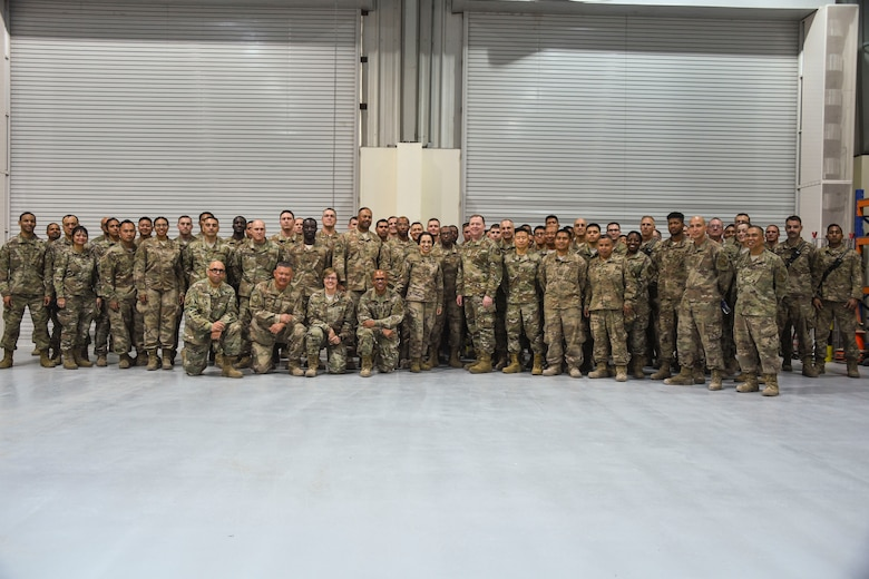 U.S. Air Force Lt. Gen. Richard Scobee, commander of Air Force Reserve Command, and Chief Master Sgt. Ericka Kelly, command chief of AFRC, pose for a photo with members of the 380th Expeditionary Civil Engineer Squadron during their visit to Al Dhafra Air Base, United Arab Emirates, Feb. 13 2019.