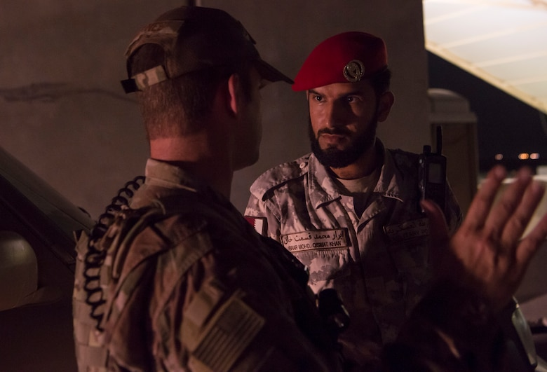 """Master Sgt. Jordan Barnes, left, 379th Expeditionary Security Forces Squadron (ESFS) combined response joint patrol leader, talks to Qatar Military Police (QMP) Soldier Ibrar Mohd. Qismat Khan, prior to conducting a """"Spartan Patrol"""" Jan. 17, 2019, at Al Udeid Air Base, Qatar. Barnes conducts Spartan Patrols, where he works side-by-side with the QMP to conduct installation perimeter checks. Together, members of 379th ESFS and QMP ensure assets and personnel are safe at Al Udeid, and there are no vulnerabilities in the installation's perimeter. (U.S. Air Force photo by Tech. Sgt. Christopher Hubenthal)"""