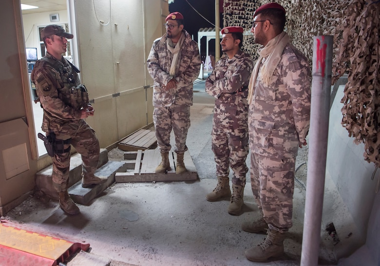 """Master Sgt. Jordan Barnes, left, 379th Expeditionary Security Forces Squadron (ESFS) combined response joint patrol leader, talks to members of the Qatar Military Police (QMP), during a """"Spartan Patrol"""" Jan. 17, 2019, at Al Udeid Air Base, Qatar. Barnes works side-by-side with the QMP to conduct the patrols, which check for vulnerabilities in the installation's perimeter. Barnes aims to perform one patrol a night to provide security and build the partnership between U.S. Air Force and Qatar Armed Forces.  (U.S. Air Force photo by Tech. Sgt. Christopher Hubenthal)"""