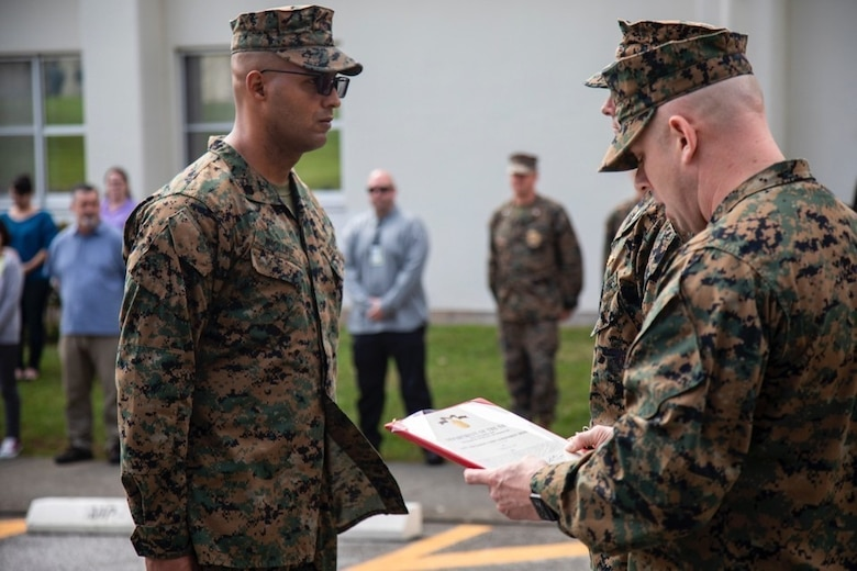 First Sergeant Jacob Karl, right, reads Staff Sgt. Jonathan McClure's, left, Navy Achievement Medal citation February 22, 2019, at Camp Foster, Okinawa, Japan. McClure was awarded the NAM for superior performance of duty while serving as a military policeman and accident investigation section chief Provost Marshal's office, H&S Bn, MCIPAC-MCB. With quick thinking and a bias for action, McClure rescued a woman from choking at a local restaurant.