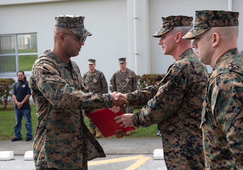 Col. Vincet Ciccoli, right, awards Staff Sgt. Jonathan McClure, left, a Navy Achievement Medal February 22, 2019, at Camp Foster, Okinawa, Japan. McClure was awarded the Navy Achievement Medal for superior performance of duty while serving as a military policeman and accident investigation section chief Provost Marshal's office, H&S Bn, MCIPAC-MCB. With quick thinking and a bias for action, McClure rescued a woman from choking at a local restaurant.