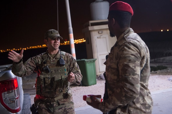 "Master Sgt. Jordan Barnes, center, 379th Expeditionary Security Forces Squadron (ESFS) combined response joint patrol leader, talks to a member of the Qatar Military Police (QMP), during a ""Spartan Patrol"" Jan. 17, 2019, at Al Udeid Air Base, Qatar. Barnes works side-by-side with the QMP to conduct the patrols, which check for vulnerabilities in the installation's perimeter. Barnes aims to perform one patrol a night to provide security and build the partnership between U.S. Air Force and Qatar Armed Forces.  (U.S. Air Force photo by Tech. Sgt. Christopher Hubenthal)"