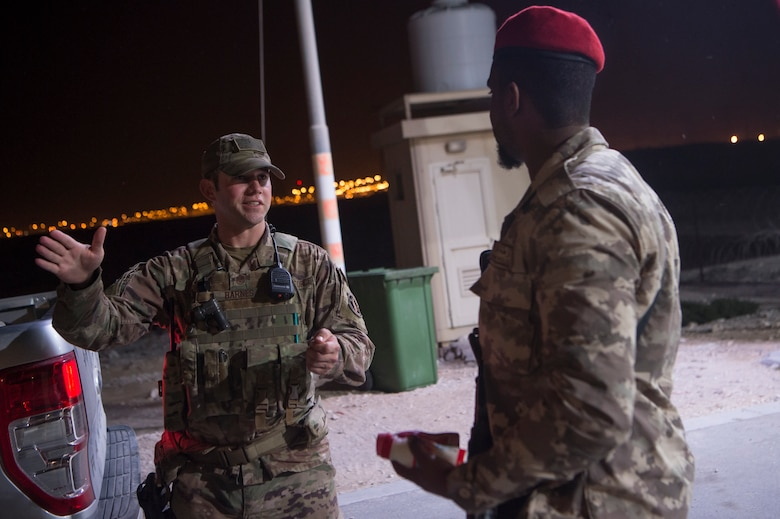 """Master Sgt. Jordan Barnes, center, 379th Expeditionary Security Forces Squadron (ESFS) combined response joint patrol leader, talks to a member of the Qatar Military Police (QMP), during a """"Spartan Patrol"""" Jan. 17, 2019, at Al Udeid Air Base, Qatar. Barnes works side-by-side with the QMP to conduct the patrols, which check for vulnerabilities in the installation's perimeter. Barnes aims to perform one patrol a night to provide security and build the partnership between U.S. Air Force and Qatar Armed Forces.  (U.S. Air Force photo by Tech. Sgt. Christopher Hubenthal)"""