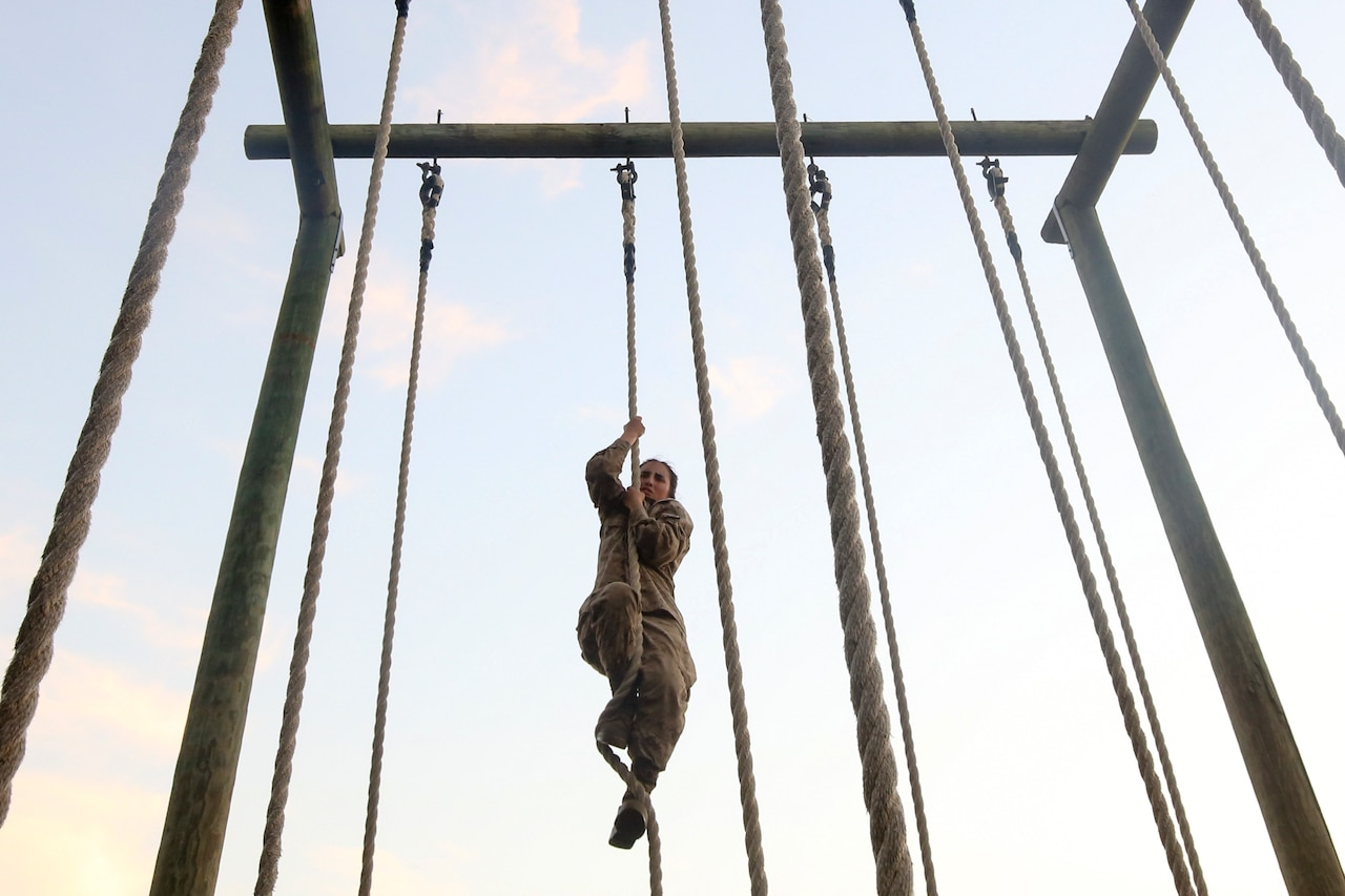 A Marine Corps recruit climbs a rope.