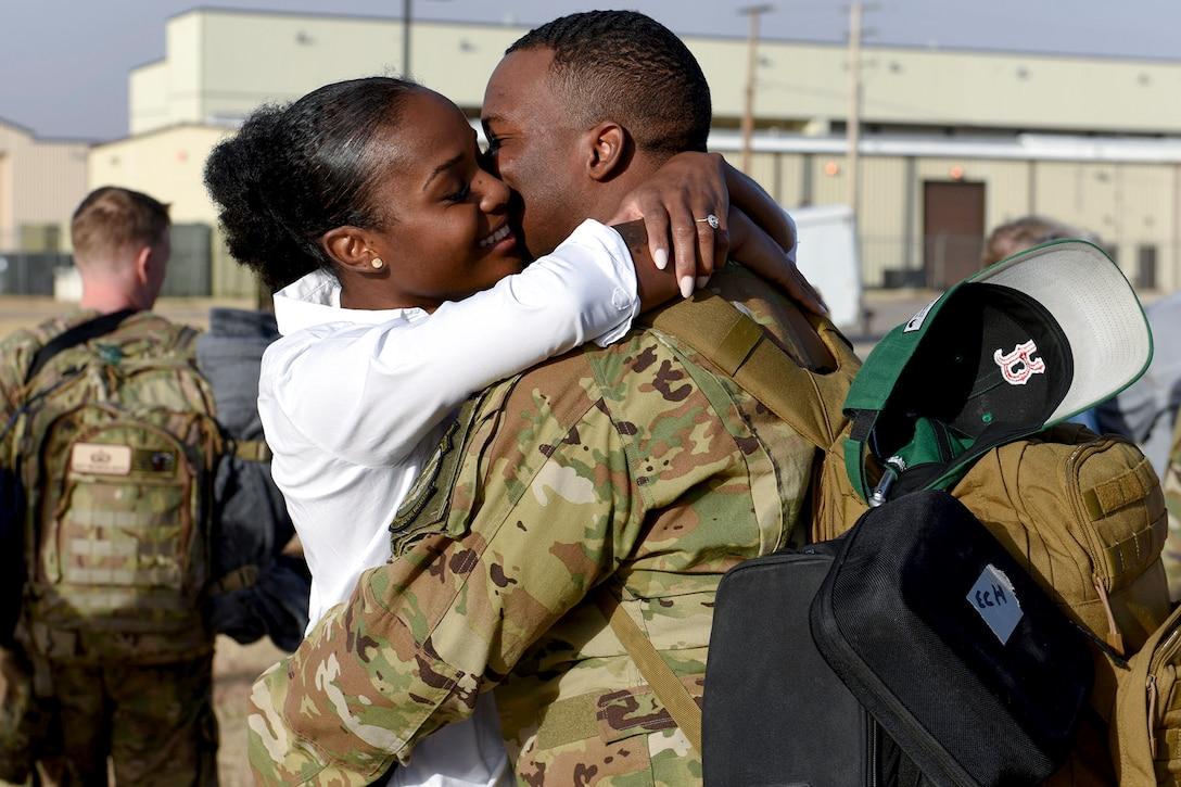 An airman hugs his wife.