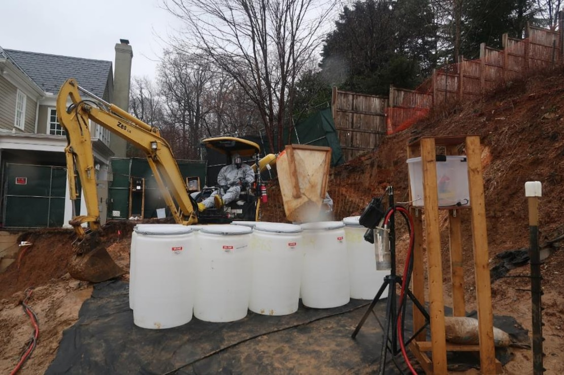 Crews fill drums with contaminated soil at 4825 Glenbrook Road during cleanup efforts there in February 2019. The 4825 Glenbrook Road cleanup effort is one ongoing aspect of the larger Spring Valley Formerly Used Defense Site.