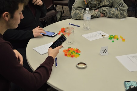 Students sitting at a round table counting gummy bears. One student is using his phone to count the gummy bears