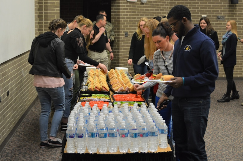 Students enjoying a catered lunch from Subway provided by the Springfield Army Recruiting Station. There is a table with students on both sides of it putting food on their plates. There are vegetable toppings, subs and water on the table as well.