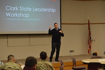 Congressman Warren Davidson speaking at the 2019 Leadership Conference and Workshop at Clark State Community College. He's wearing a black sweater vest with tie. There are soldiers sitting in front of him wearing multicam uniforms. There is a giant screen with the words 2019 Leadership Conference and Workshop behind the Congressman.