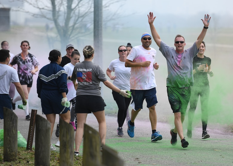 U.S. Air Force Col. Richard McClure, 81st Dental Squadron commander, leads a line of Keesler personnel through colored powder during a Run For Your Life Color Run 5K through marina park at Keesler Air Force Base, Mississippi, Feb. 21, 2019. The event, which was held in support of suicide prevention awareness, allowed participants to detour from the course and get showered with different colored powders as it was tossed in the air. A portion of the t-shirt sale proceeds will be donated to the American Foundation for Suicide Prevention and the Keesler Airman's Ball. (U.S. Air Force photo by Kemberly Groue)