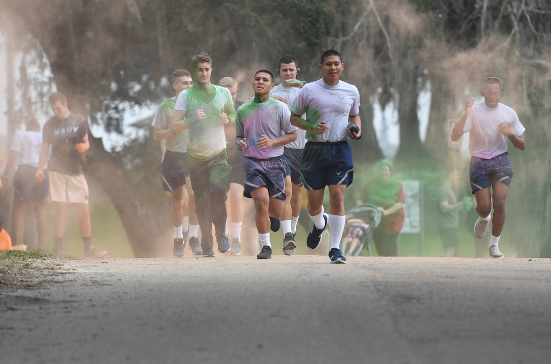 Airmen from the 338th Training Squadron and other Keesler personnel get colored powder thrown at them during a Run For Your Life Color Run 5K through marina park at Keesler Air Force Base, Mississippi, Feb. 21, 2019. The event, which was held in support of suicide prevention awareness, allowed participants to detour from the course and get showered with different colored powders as it was tossed in the air. A portion of the t-shirt sale proceeds will be donated to the American Foundation for Suicide Prevention and the Keesler Airman's Ball. (U.S. Air Force photo by Kemberly Groue)