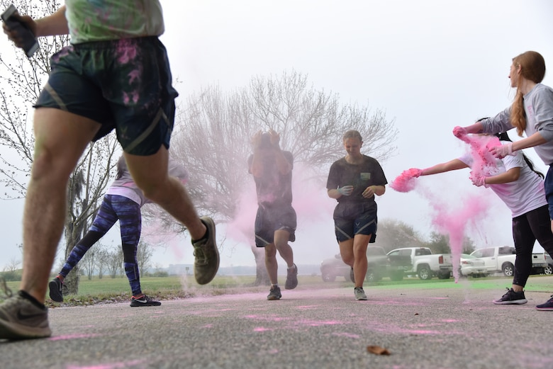 Keesler personnel get colored powder thrown at them during a Run For Your Life Color Run 5K through marina park at Keesler Air Force Base, Mississippi, Feb. 21, 2019. The event, which was held in support of suicide prevention awareness, allowed participants to detour from the course and get showered with different colored powders as it was tossed in the air. A portion of the t-shirt sale proceeds will be donated to the American Foundation for Suicide Prevention and the Keesler Airman's Ball. (U.S. Air Force photo by Kemberly Groue)