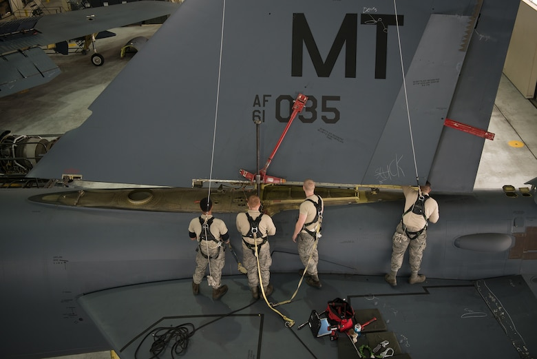Crew chiefs assigned to the 5th Maintenance Squadron lower the vertical stabilizer on a B-52H Stratofortress at Minot Air Force Base, North Dakota, Feb. 10, 2019.