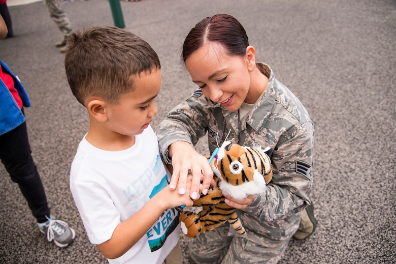 U.S. Air Force Senior Airman Shinique Manders, 23d Aeromedical Dental Squadron, helps a child use a toothbrush during a visit to the Child Development Center  at Moody Air Force Base, Georgia, Feb. 22, 2019. February is National Children's Dental Health Month, a national health observance that brings together thousands of dedicated professionals, health care providers, and educators to promote the benefits of good oral health to children. (U.S. Air Force Photo by Andrea Jenkins)
