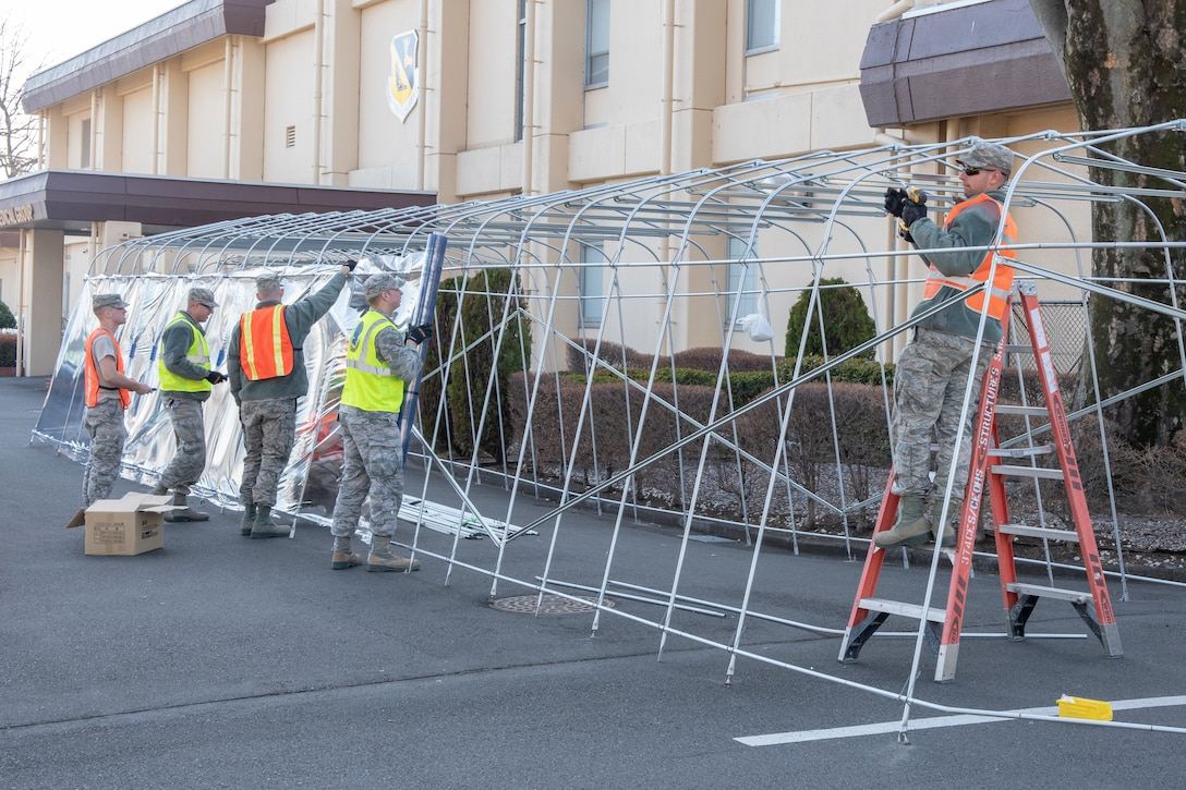 Airmen from the 374th Civil Engineer Squadron work together to secure the weather-resistant coating of a temporary corridor at Yokota Air Base, Japan, Feb. 21, 2019.