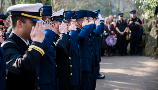 Members of the U.S. Air Force, Navy, and Army render a salute to the Mi Amigo memorial at Sheffield, United Kingdom, February 24th, 2019. This year's annual memorial service was accompanied by a United States Air Force and Royal Air Force flypast in Endcliffe Park two days prior, where thousands of U.K. residents honored the memory of ten fallen U.S. Airmen who died when their war-crippled B-17 Flying Fortress crash landed to avoid killing residents and nearby children. (U.S. Air Force photo by Tech Sgt. Aaron Thomasson)
