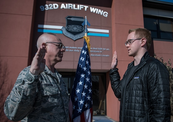 "Enlisting into the U.S. Air Force Reserve Command is Casey Earl, right, being given the oath of enlistment by Lt. Col.Stan Paregien, 932nd Airlift Wing Public Affairs Officer, Feb. 25, 2019, 932nd AW headquarters building, Scott Air Force Base, Illinois. Earl will be an E-5, Staff Sgt. For a short time and then begin his Air Force journey to becoming an officer in Cyber Operations. ""I chose the Air Force Reserve because it positioned me for great opportunities that matched my civilian career,"" said Earl about why he became a citizen Airman.  (U.S. Air Force photo by Christopher Parr)"