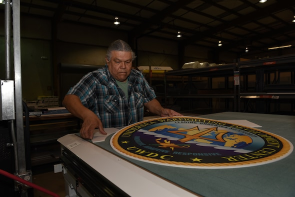 Carlos Castro, Defense Logistics Agency, showcases a large decal Feb. 7, 2019, at Travis Air Force Base, Calif., after the decal was cut by a flatbed cutter. The Travis DLA facility provides a variety of printing services to federal agencies and government offices. (U.S. Air Force photo by Tech. Sgt. James Hodgman)
