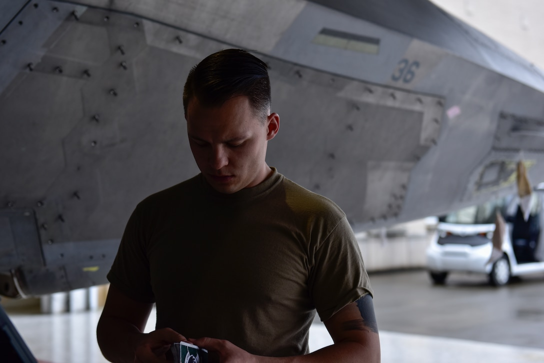 U.S. Air Force Staff Sgt. Jackson Findlay, Tyndall Air Force Base, Fla., 325th Maintenance Squadron crew chief, reviews his notes from the previous days log prior to completing routine maintenance on an F-22 Raptor at Eglin AFB. Fla., Feb. 21, 2019. Some of the F-22s that were stationed at Tyndall AFB were evacuated to Eglin AFB hangars where its' dedicated crews maintain them until Tyndall hangars are restored. (U.S. Air Force photo by Staff Sgt. Alexandre Montes)