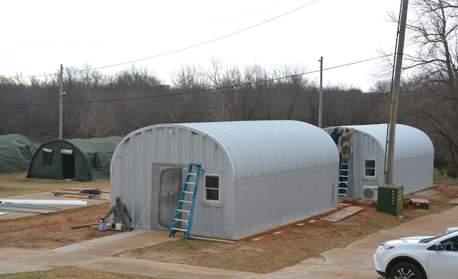 Members of the 507th Civil Engineer Squadron work on the final touches of three new Quonset huts at the Glenwood training area here February 26. Reserve Citizen Airmen partnered with the 72nd Air Base Wing to build the huts and repair some damaged facilities at the training area. The new Quonset huts are more permanent, cheaper, and fully equipped with electric, heating and air. The improvements will make readiness training exercises on the site more efficient, according to members of the wing inspection team. (U.S. Air Force Photo by Maj. Jon Quinlan)