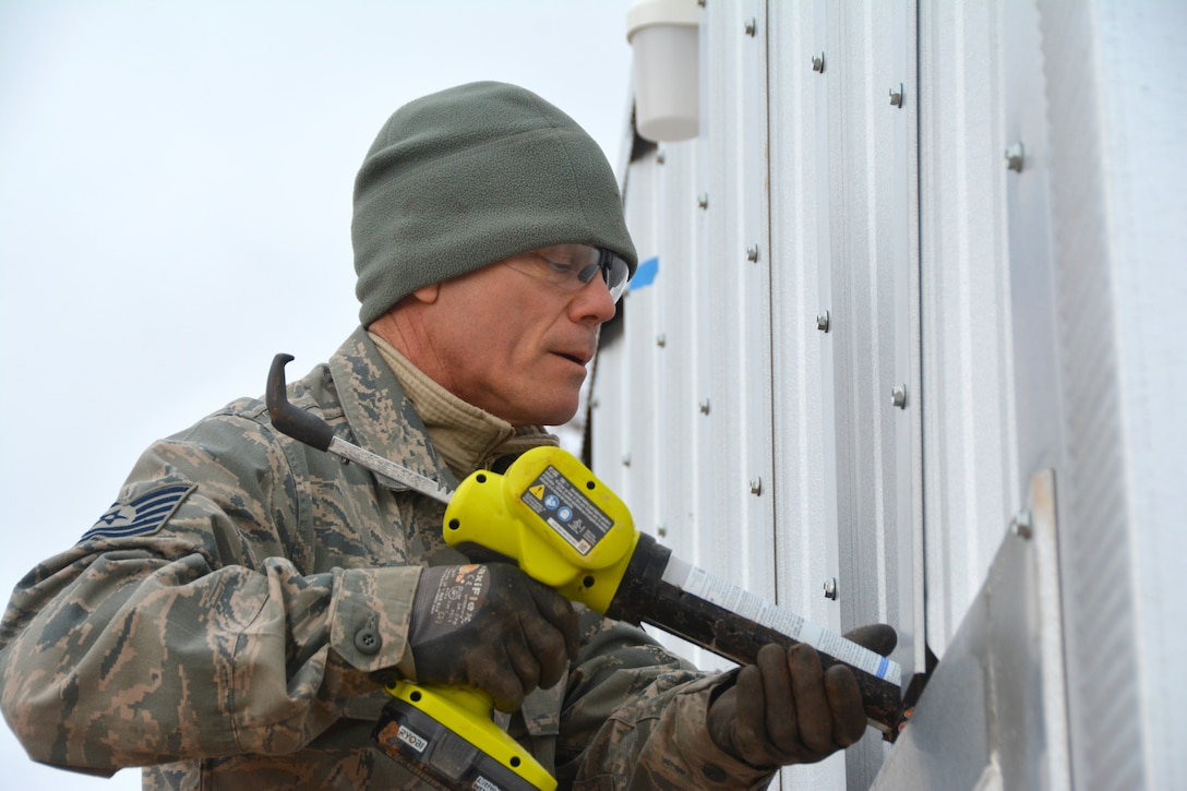 Tech. Sgt. Lyndon Jones, 507th Civil Engineer Squadron works on the final touches of one of the three new Quonset huts at the Glenwood training area here February 26. Reserve Citizen Airmen partnered with the 72nd Air Base Wing to build the huts and repair some damaged facilities at the training area. The new Quonset huts are more permanent, cheaper, and fully equipped with electric, heating and air. The improvements will make readiness training exercises on the site more efficient, according to members of the wing inspection team. (U.S. Air Force Photo by Maj. Jon Quinlan)