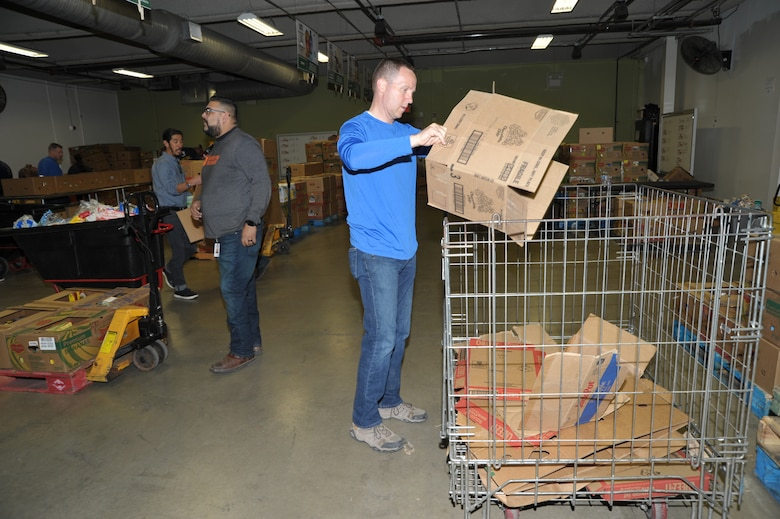 340th Superintendent Chief Master Sgt. Scott Goetze breaks down boxes for recycling during the 340th FTG's Feb. 22 community outreach event in support of the San Antonio Foodbank. Together, the 340th team and fellow volunteers sorted and packed more than 10,000 pounds of food and non-food items, including pet supplies. (U.S. Air Force photo by Debbie Gildea)