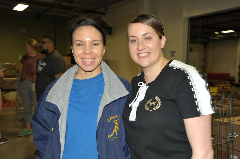 Master Sgt. Angelina Manby (left) and Tech. Sgt. Kassandra Farani pose for a pic at the end of the 340th FTG's Feb. 22 community outreach event in support of the San Antonio Foodbank. Manby and Farani organized the event, during which the 340th team and fellow volunteers sorted and packed more than 10,000 pounds of food and non-food items, including pet supplies. (U.S. Air Force photo by Debbie Gildea)