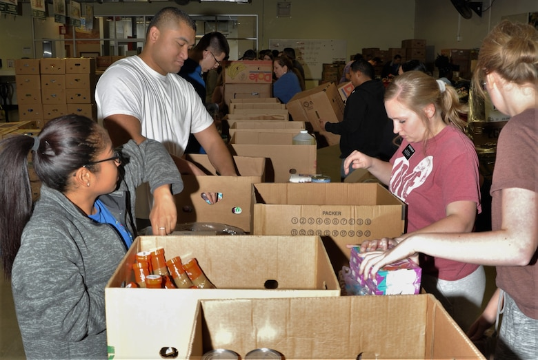 Master Sgt. Natasha Todd (left) and Tech. Sgt. Amosa Farani (white shirt) work alongside volunteers from other San Antonio-area organizations to sort and box food during the 340th FTG's Feb. 22 community outreach event in support of the San Antonio Foodbank. Together, the 340th team and fellow volunteers sorted and packed more than 10,000 pounds of food. (U.S. Air Force photo by Debbie Gildea)