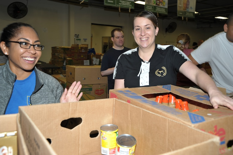 Master Sgt. Natasha Todd and Tech. Sgt. Kassandra Farani share a fun moment while sorting and packing food during the 340th FTG's Feb. 22 community outreach event in support of the San Antonio Foodbank. Together, the 340th team and fellow volunteers sorted and packed more than 10,000 pounds of food. (U.S. Air Force photo by Debbie Gildea)