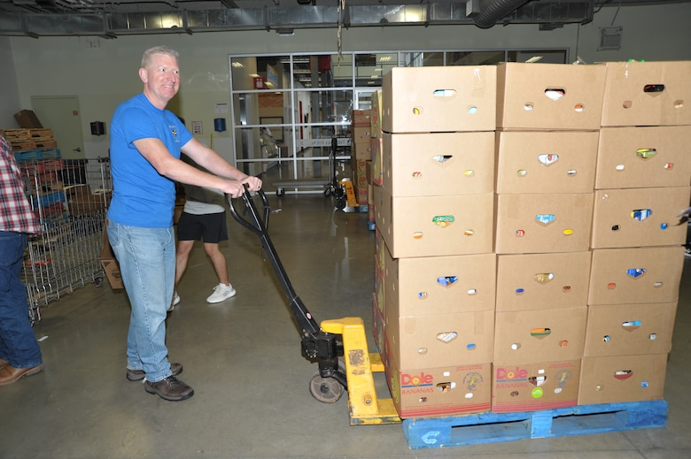Senior Master Sgt. Craig Pfister, 340th inspections superintendent, prepares to haul a palette of sorted food to the warehouse during the 340th FTG's Feb. 22 community outreach event in support of the San Antonio Foodbank. Together, the 340th team and fellow volunteers sorted and packed more than 10,000 pounds of food and non-food items, including pet supplies. (U.S. Air Force photo by Debbie Gildea)