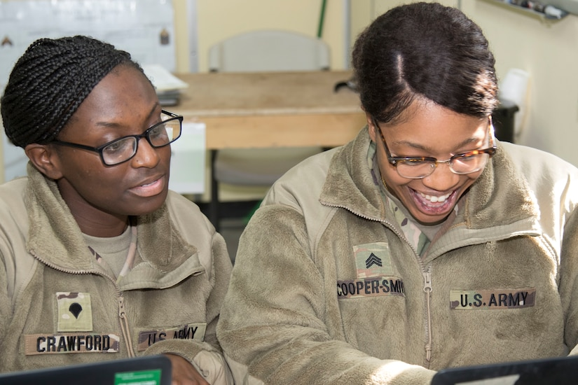 """Specialist Marticha Crawford, left, and Sgt. Denay Cooper-Smith, both students at Camp Buehring, Kuwait's Basic Leader Course, work together during a small group exercise Feb. 16, 2019. """"Working together helps build comradery among all of us; it also helps us complete tasks more efficiently,"""" said Crawford."""