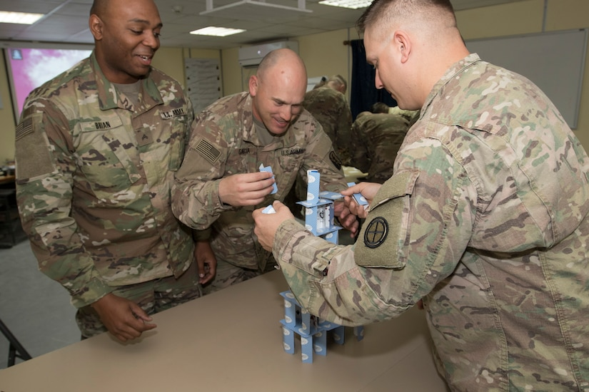 From left, Cpl. Derick Brian, Sgt. Tomas Garcia, and Cpl. Joshua Roth, who are all students at Camp Buehring, Kuwait's Basic Leader Course, build a tower of cards during a group exercise Feb. 17, 2019. Activities, such as building a tower of cards, allow Soldiers to work as a team and build comradery.