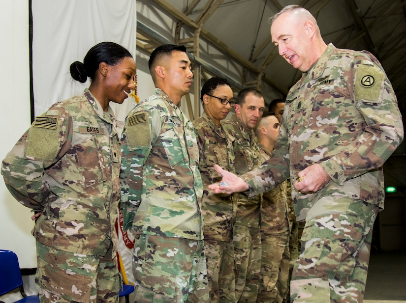 Command Sgt. Maj. Dan Churchman, commandant, Basic Leader Course, Camp Buehring, Kuwait, presents a Commandants Coin to Spc. Shannon Gates, far left, Company A, 106th Brigade Support Battalion, 155th Armored Brigade Combat Team, Mississippi Army National Guard, who is from Magee, Mississippi, for earning BLCs distinguished honor graduate, Feb. 19, 2019. Distinguished honor graduate is awarded to the student who holds the highest overall grade point average throughout the course.