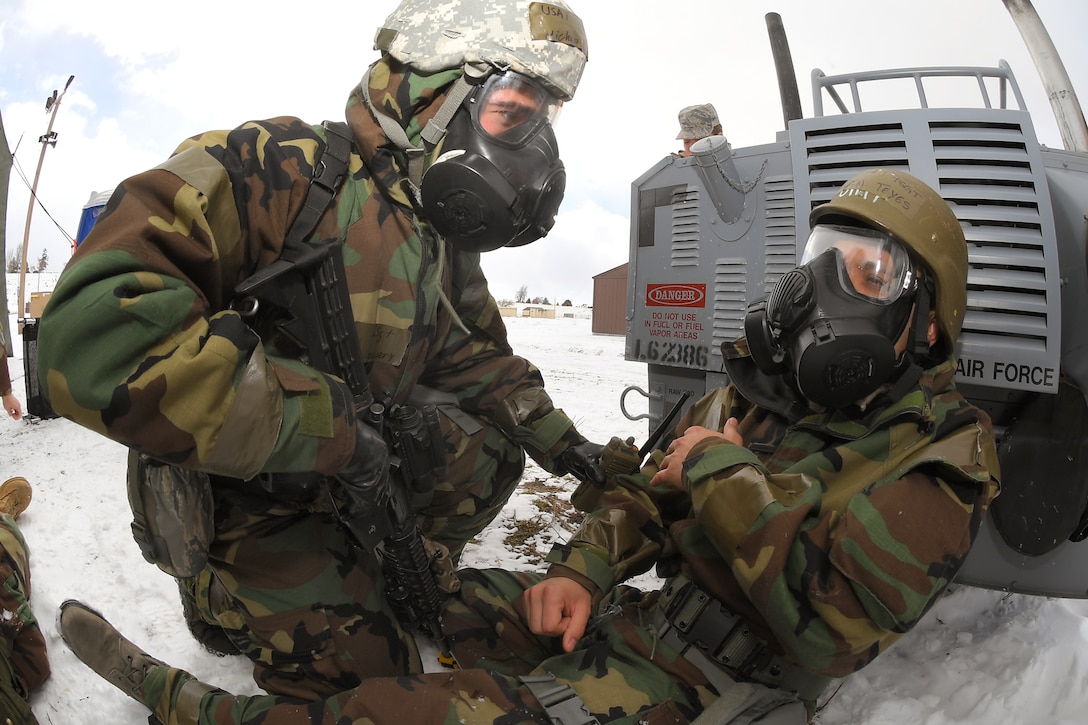 Staff Sgt. Nicholas Lowery, 75th Security Forces Squadron, provides assistance to Tech. Sgt. Marvin Teyes, 75th Air Base Wing, during a readiness exercise, Feb. 7, 2019, at Hill Air Force Base, Utah. During the exercise, Airmen donned mission-oriented projective posture, or MOPP, gear and were assessed on performing different tasks in a simulated toxic environment to improve their operational readiness. (U.S. Air Force photo by Todd Cromar)
