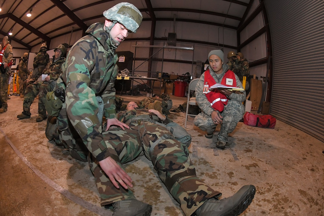 A wing inspection team member evaluates an Airman attending to a patient with simulated injuries during a readiness exercise, Feb. 7, 2019, at Hill Air Force Base, Utah. During the exercise, Airmen were assessed on different tasks to improve their operational readiness. (U.S. Air Force photo by Todd Cromar)