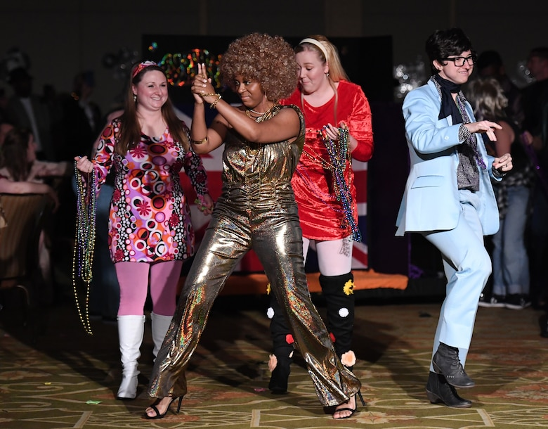 Members of the 81st Medical Operations Squadron portray the Austin Powers cast as they make their way down the aisle during the 31st Annual Krewe of Medics Mardi Gras Ball at the Bay Breeze Event Center on Keesler Air Force Base, Mississippi, Feb. 23, 2019. The Krewe of Medics hosts a yearly ball to give Keesler Medical Center personnel a taste of the Gulf Coast and an opportunity to experience a traditional Mardi Gras, which is celebrated by the local communities. The theme for this year's ball was Hollywood vs. Broadway. (U.S. Air Force photo by Kemberly Groue)