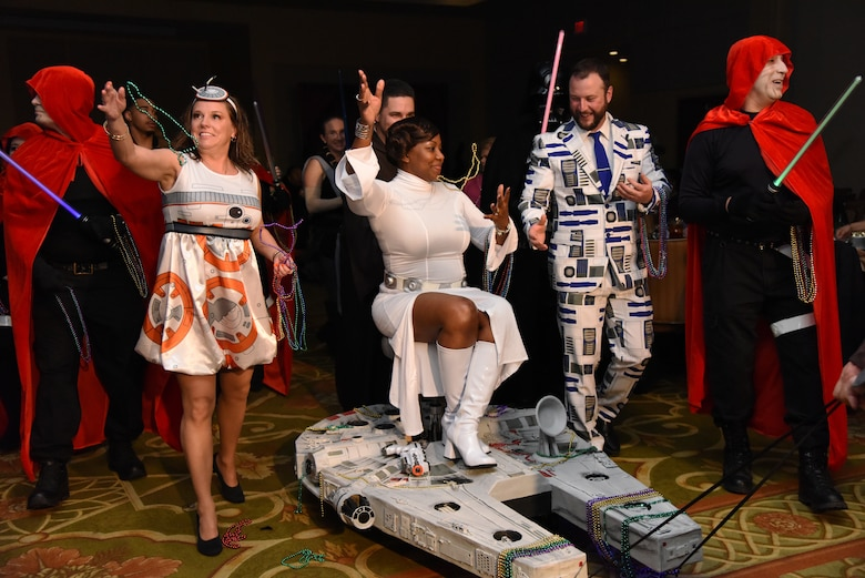Members of the 81st Surgical Operations Squadron portray the Star Wars cast as they make their way down the aisle during the 31st Annual Krewe of Medics Mardi Gras Ball at the Bay Breeze Event Center on Keesler Air Force Base, Mississippi, Feb. 23, 2019. The Krewe of Medics hosts a yearly ball to give Keesler Medical Center personnel a taste of the Gulf Coast and an opportunity to experience a traditional Mardi Gras, which is celebrated by the local communities. The theme for this year's ball was Hollywood vs. Broadway. (U.S. Air Force photo by Kemberly Groue)