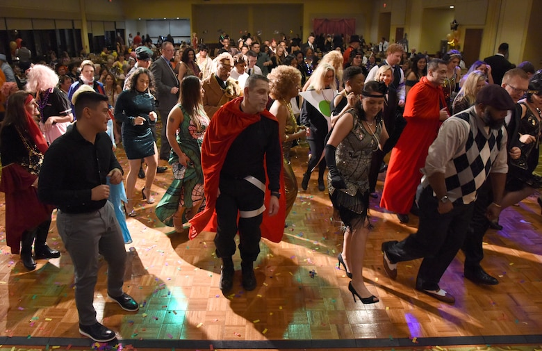 Members of the 81st Medical Group dance during the 31st Annual Krewe of Medics Mardi Gras Ball at the Bay Breeze Event Center on Keesler Air Force Base, Mississippi, Feb. 23, 2019. The Krewe of Medics hosts a yearly ball to give Keesler Medical Center personnel a taste of the Gulf Coast and an opportunity to experience a traditional Mardi Gras, which is celebrated by the local communities. The theme for this year's ball was Hollywood vs. Broadway. (U.S. Air Force photo by Kemberly Groue)